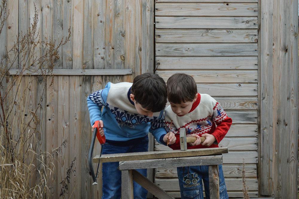 copii lucrand cu ciocan si ferastrau pe un suport vechi din lemn